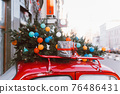 Red retro car with a Christmas tree fir tied to the roof. 76486431