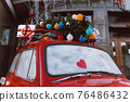 Red retro car with a Christmas tree fir tied to the roof. 76486432