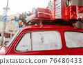 Red retro car with a Christmas tree fir tied to the roof. 76486433