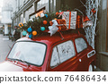 Red retro car with a Christmas tree fir tied to the roof. 76486434
