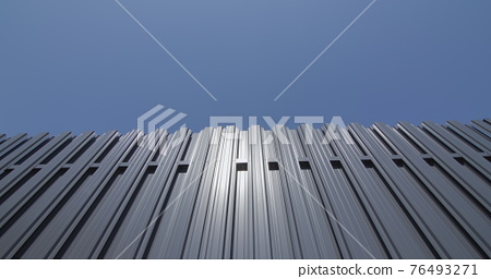 Grey metal shuttle fence against blue sky 76493271