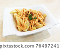 Close Up French Fries with Cheese On Table. 76497241