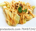 Close Up French Fries with Cheese On White Plate. 76497242