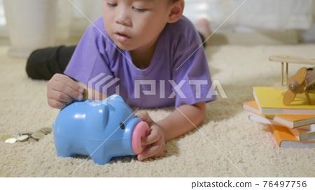 kid boy preschool putting pin money coins into blue faced piglet slot 76497756