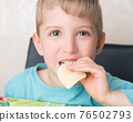 Kid is eating chips and smiling 76502793