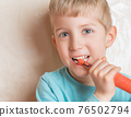 Kid smiling and brushing her teeth close up 76502794