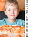 Five year old boy smiling and eats pizza sitting at black chair 76502818