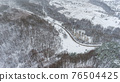 Aerial view on the road and forest at the winter time. Natural winter landscape from air. Forest under snow a the winter. 76504425