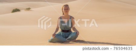 BANNER, LONG FORMAT Desert meditation. Young beautiful woman traveling in the desert. Sandy dunes and blue sky on sunny summer day. Travel, adventure, freedom concept. Tourism reopens after quarantine 76504635
