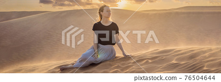 BANNER, LONG FORMAT Young beautiful woman traveling in the desert. Sandy dunes and blue sky on sunny summer day. Travel, adventure, freedom concept. Tourism reopens after quarantine COVID 19 76504644