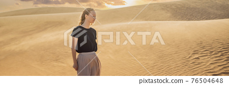 BANNER, LONG FORMAT Young beautiful woman traveling in the desert. Sandy dunes and blue sky on sunny summer day. Travel, adventure, freedom concept. Tourism reopens after quarantine COVID 19 76504648