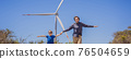 BANNER, LONG FORMAT Alternative energy, wind farm and happy time with your family. Happy father on the road with his son on vacation and escape to nature. Father and son waving their arms like a 76504659