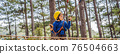 BANNER, LONG FORMAT Happy child in a helmet, healthy teenager school boy enjoying activity in a climbing adventure park on a summer day 76504663