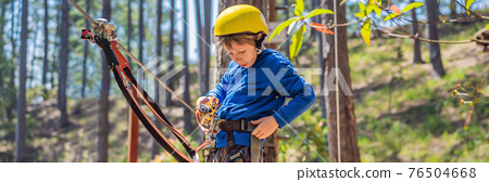 BANNER, LONG FORMAT Happy child in a helmet, healthy teenager school boy enjoying activity in a climbing adventure park on a summer day 76504668