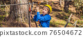 BANNER, LONG FORMAT Happy child in a helmet, healthy teenager school boy enjoying activity in a climbing adventure park on a summer day 76504672