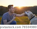 Man teaching his dog on meadow at sunset 76504980