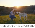 Man teaching his dog on meadow at sunset 76504982