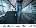 Man walking with suitcase at airport terminal 76505078