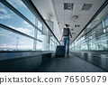 Man walking with suitcase at airport terminal 76505079