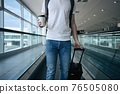 Man walking with paper coffee cup at airport terminal 76505080