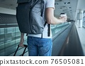 Man walking with paper coffee cup at airport terminal 76505081