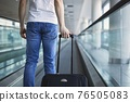 Man walking with suitcase at airport terminal 76505083