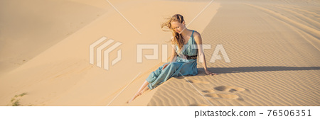 BANNER, LONG FORMAT Young beautiful woman traveling in the desert. Sandy dunes and blue sky on sunny summer day. Travel, adventure, freedom concept. Tourism reopens after quarantine COVID 19 76506351