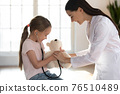 Playful nurse play with little girl patient 76510489