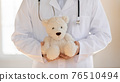 Close up of male doctor pose with teddy bear toy 76510494