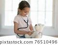 Cute little girl play hospital with teddy bear toy 76510496
