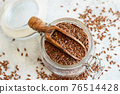 Raw Flax seeds in a jar with a scoop 76514428
