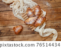 French fresh crusty croissants on a wooden table top view 76514434