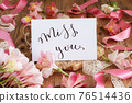 MISS YOU card on a wooden table between pink flowers 76514436