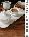 Coffee cup and cookies on a tray on wooden table 76514441