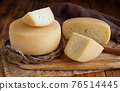 Pieces of  fresh homemade cheese on a wooden board top view 76514445