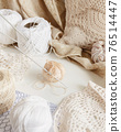 Cotton thread and hook on a table surrounded by cotton balls and doilies 76514447