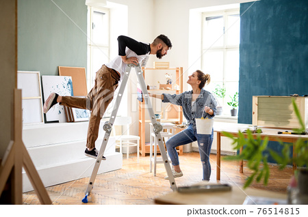 Mid adults couple having fun when painting indoors at home, relocation and diy concept. 76514815