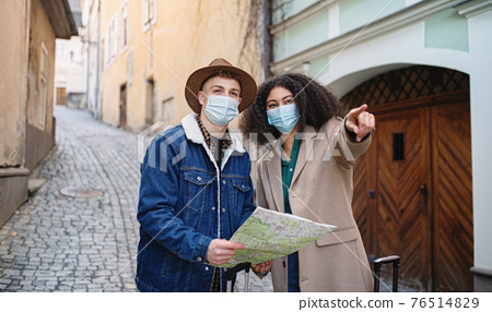 Young couple tourists with map on holiday in old town, coronavirus concept. 76514829