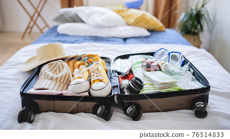 Open suitcase packed for holiday on bed at home, coronavirus concept. 76514833
