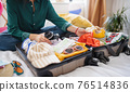 Unrecognizable woman with suitcase packing for holiday at home, coronavirus concept. 76514836