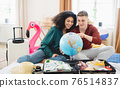Young couple with map packing for holiday at home. 76514837