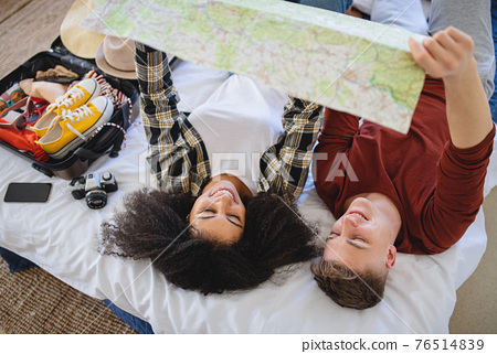 Young couple with map packing for holiday at home. 76514839