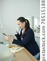 Businesswoman checking smartphone 76515188