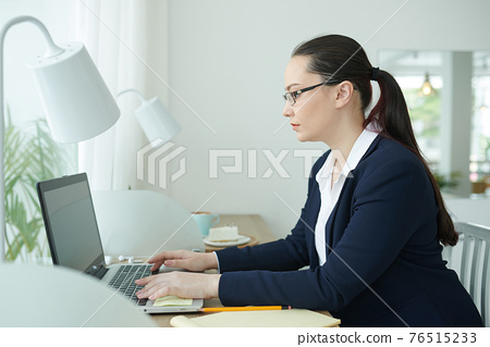 Female entrepreneur working on laptop 76515233