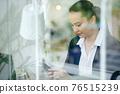 Businesswoman checking smartphone 76515239