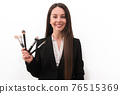 girl with makeup with long dark hair in a business suit holding a brush in his hand, on a white background 76515369