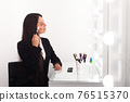 girl, makeup artist, with long dark hair in a business suit sits at the makeup table, puts powder on her face and smiles in a bright room, office 76515370