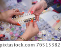 Counter in the mall with a product for nail service, palettes with samples of nail design 76515382