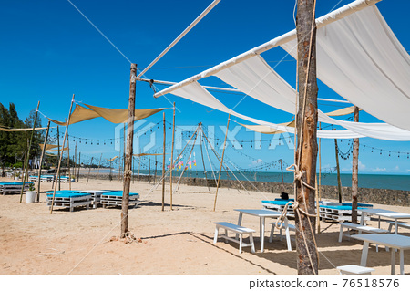 Relax cafe seats on white sand beach in summer 76518576