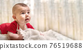 A newborn healthy baby, a boy of four months, lies on his stomach, resting happily. Against the background of the bedroom room. 76519688